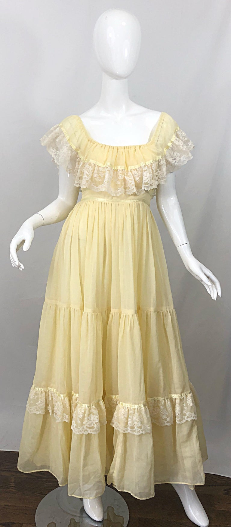 Amazing 1970s pale yellow and white cotton voile and lace boho empire maxi dress! Features white lace around the bodice and at the ruffle hem. Can be worn on or off the shoulders. Flattering empire waist is easy to wear. Ties at back waist can