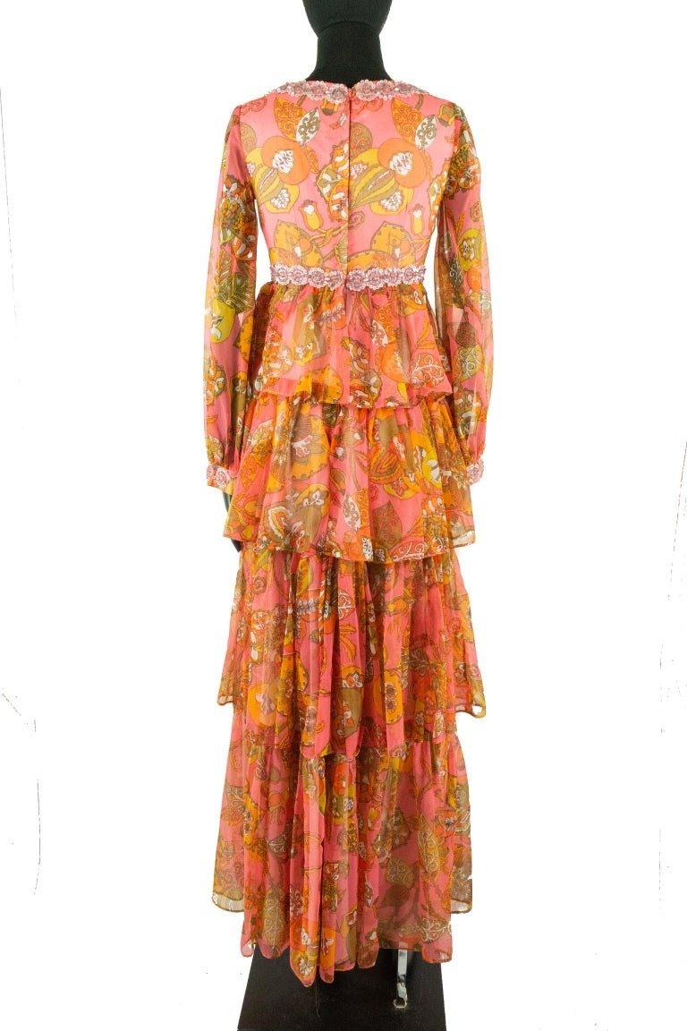 A Vintage 1970s Pauline dress; featuring a coral psychedelic print of peach and white flower swirling into golden-brown leaves. The bodice features a scooped neckline and empire waistline, both of which are embellished with small roses made of