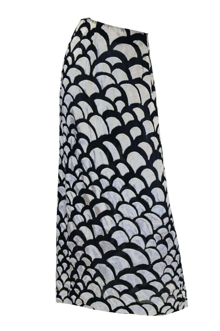 Simply astounding evening dress ensemble by Pauline Trigere. The ensemble consists of a dramatic skirt and matching cardigan. The skirt is maxi length with an A - line silhouette and narrow waistband. The cardigan is hip length, with long sleeves