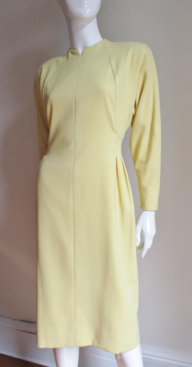 A pretty lemon yellow light weight wool dress from Pauline Trigere.  It has a notched crew neckline, light shoulder padding and dolman sleeves with zipper cuffs.  There is angled seaming on the bodice front and back creating flattering lines and the