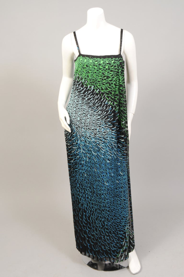 A spectacular print is used for this silk chiffon faux wrap style evening dress and oversized shawl from Pauline Trigere circa 1970. The colors range from palest blue to emerald green to brilliant turquoise, all on a ribbon weave silk chiffon. The