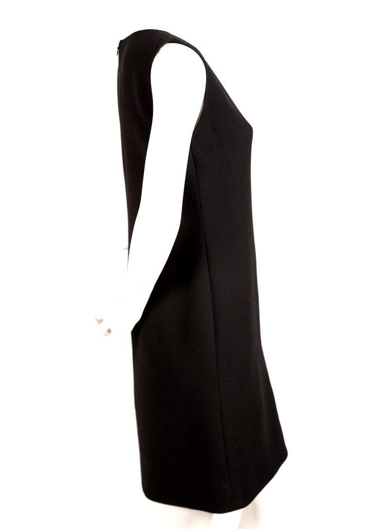 Black wool haute couture dress with circular cut-outs backed in red wool, designed by Pierre Cardin. Sleek shape falls from the shoulders to the hem skimming the body. Approximate measurements: bust 34
