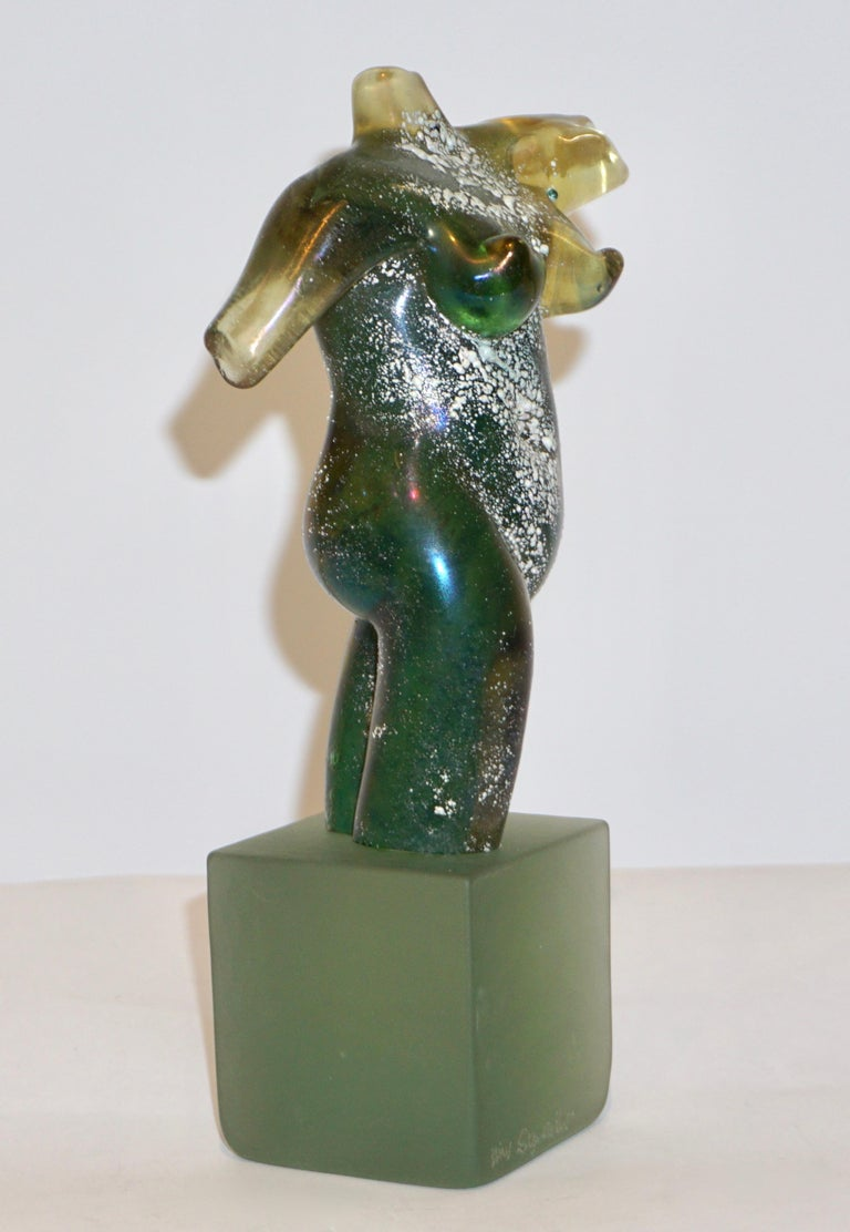 An exquisite vintage Work of Art signed Pino Signoretto, an iridescent nude sculpture in a sophisticated aqua green blown Murano glass, textured with the technique scavo that creates shimmering reflections and gives movement to the piece, raised on