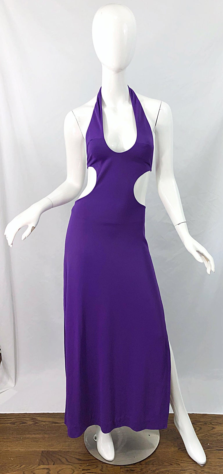 Sexy 1970s purple cut - out disco maxi dress ! Features the perfect true purple color. Ties at back neck. Cut-out at each side of the waist reveals just the right amount of skin. Hidden zipper up the back. Slit up the left side of the leg. Can