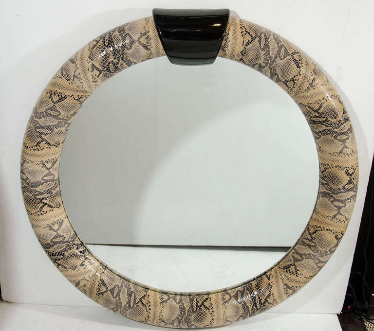 Mid-Century Modern round mirror wrapped in stunning embossed leather with snakeskin design. Python print leather with lacquered ebonized wood pediment top.