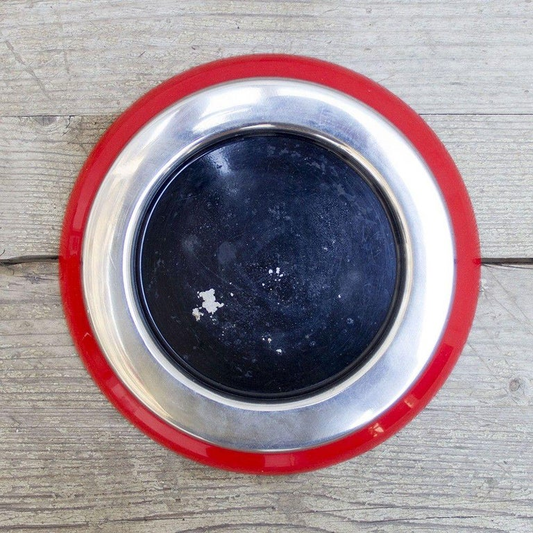 A cherry red ABS plastic base, featuring a chrome metal rim around a black enamel plate. This 1970s ashtray was designed by Sergio Asti for the furniture and decorative manufacture Kartell.