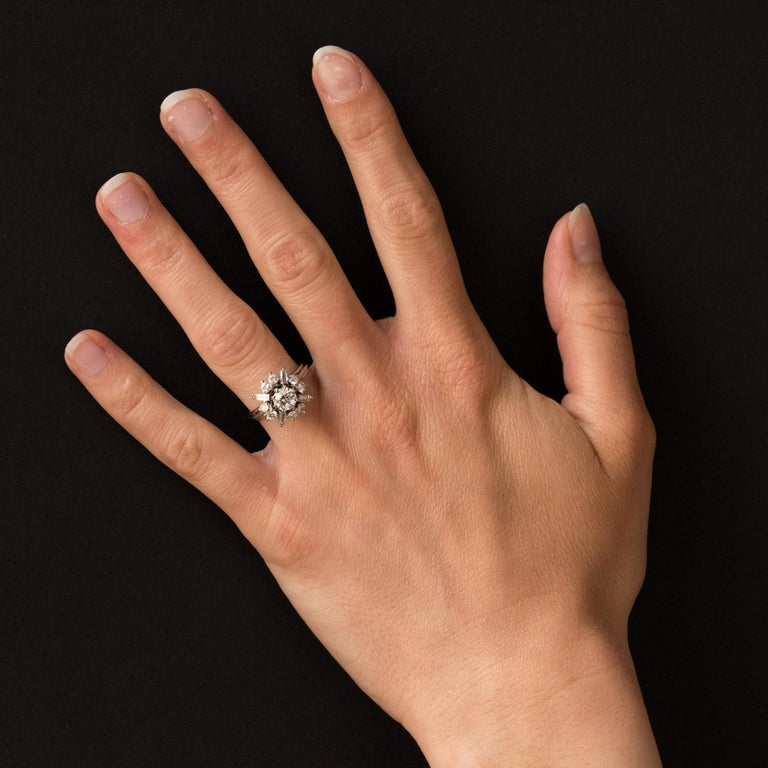 Platinum ring. Bright and so vintage, this retro ring is set with diamonds of different sizes: large brilliant in the center, smaller brilliant and baguette around. The head made of platinum wire go on the mount which is composed of 3 platinum