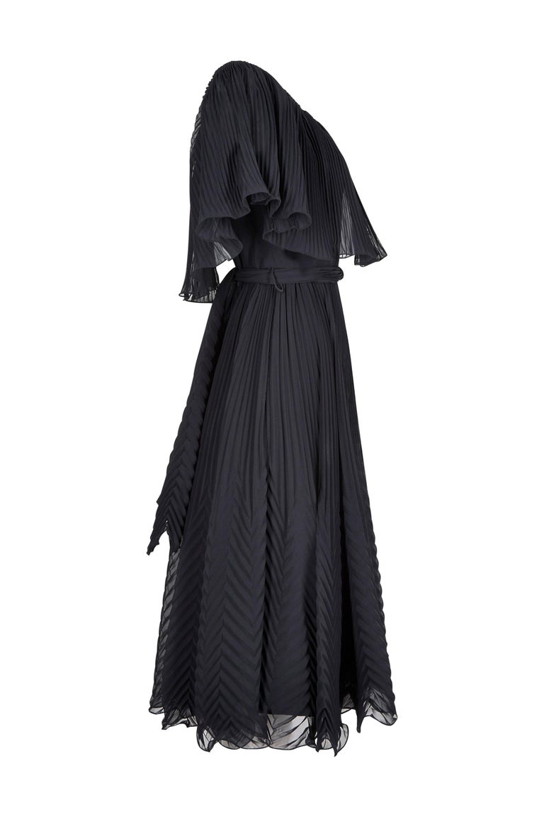 This vivacious 1970s black pleated chiffon cocktail dress is by Roland Klein for Marcel Fenez and is charming, feminine and in excellent vintage condition. The dress is comprised of a black crepe underlay cut into a simple shift style silhouette