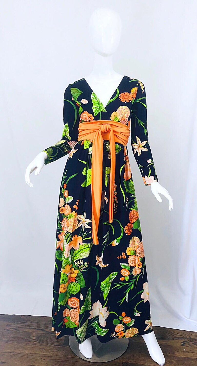 Amazing 1970s RONALD KOLODZIE navy blue, orange and green long sleeve jersey maxi dress! Features a tropical Hawaiian print in vibrant colors of neon orange, green, peach and light pink throughout on a navy blue background. Attached obi sash detail