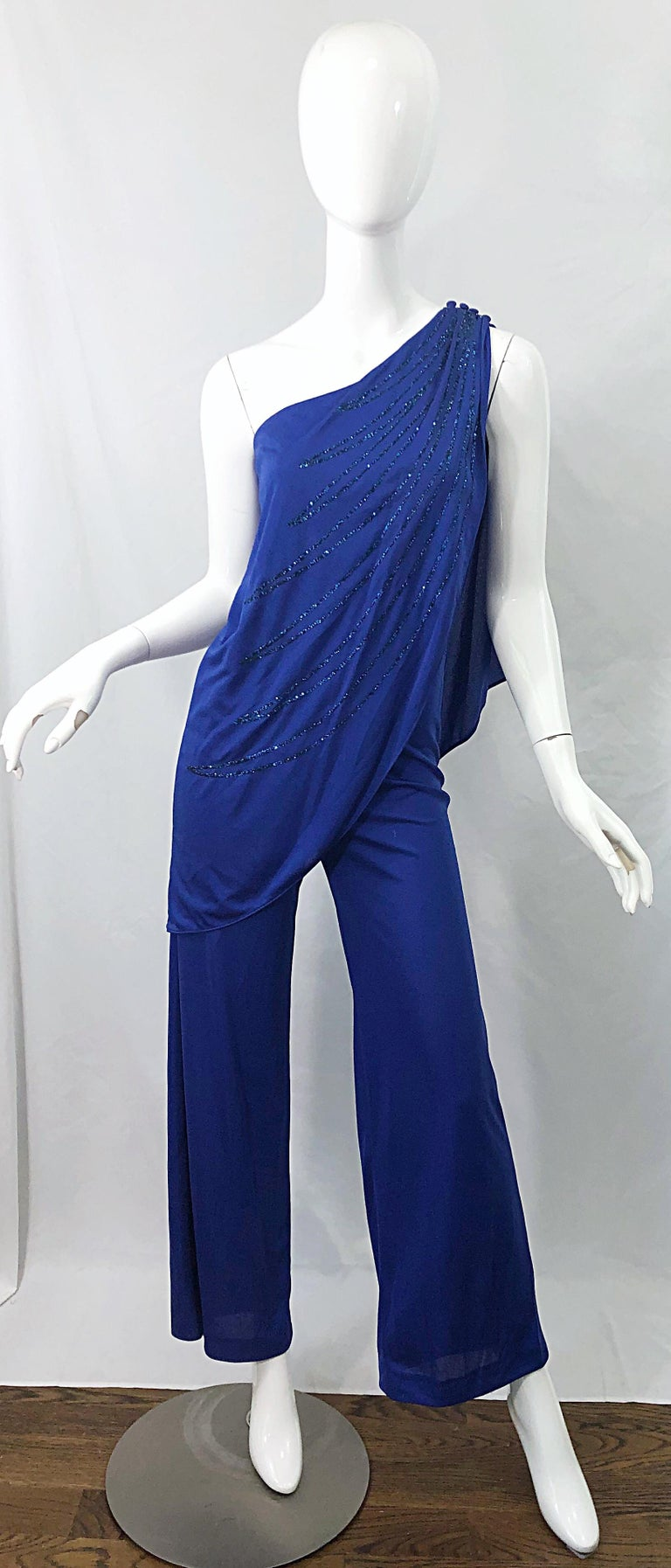 Amazing slinky late 70s SAMIR blue one shoulder Grecian style disco jumpsuit ! Features one left shoulder with attached drape, which is encrusted with glitter (not the messy kind) in the front and back. Flared bell bottom legs. Hidden zipper up the
