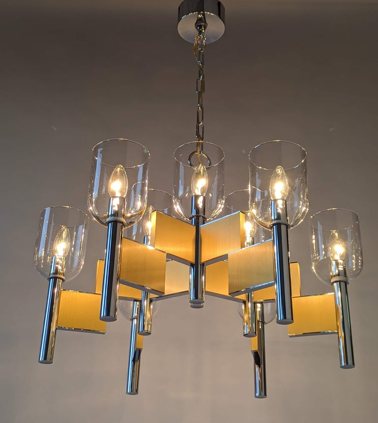 Mouth blowed glass hurricane chandelier made of thick chromed steel and brass.   Prime quality material, solid construction.  Chandelier measure 25 in. wide by 19 in. high.  Chain length with canopy 16 in. high. Could be adjusted.  9 E12 candelabra