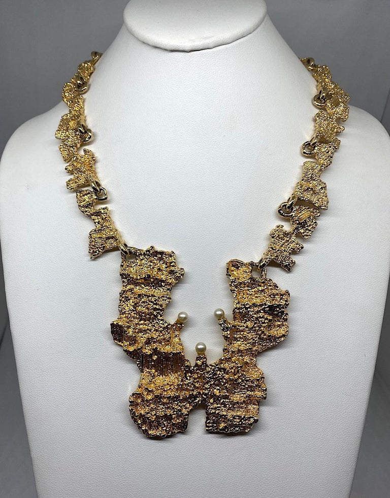 A wearable pieces sculpture is this 1970s brutalist gold plate necklace. The pendant and links are sculpted with a rough gold nugget texture in gold plate and accented with three faux pearls. The large pendant is 3.25 inches wide and 3.38 inches