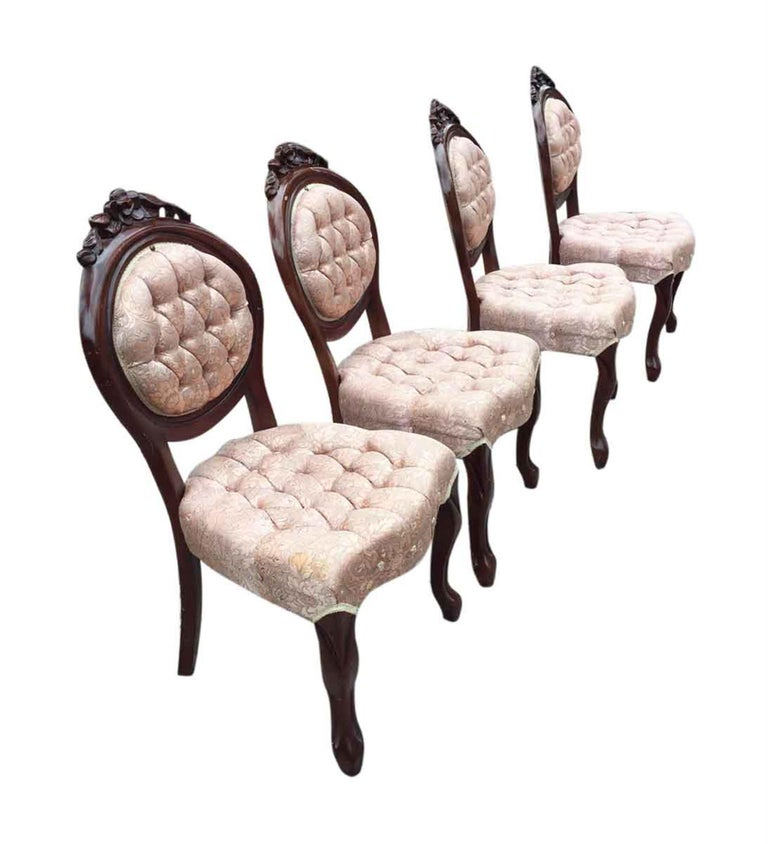 Four 1970s carved dark wood toned French dining room chairs with tufted pink floral silk upholstery, brass rivets, and floral detail in the frame. Priced as a set. This can be seen at our 2420 Broadway location on the upper west side in Manhattan.