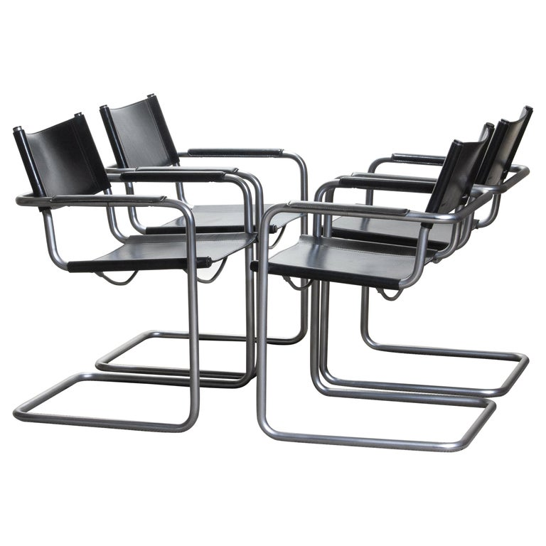 1970. Perfect set of four dining / office chairs made by Matteo Grassi, Italy. The chairs have tubular titanium look steel frames with sturdy black leather seating and backrest. They are signed on the back of the backrest. Overall condition is