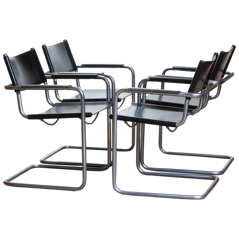 1970, perfect set of four dining or office chairs made by Matteo Grassi, Italy. The chairs have tubular titanium look steel frames with sturdy black leather seating and backrest. They are signed on the back of the backrest. Overall condition is