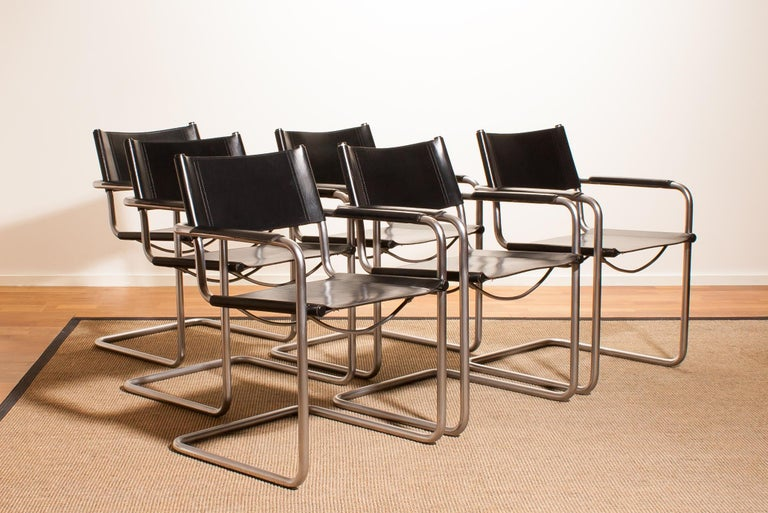 A beautiful set of six dining chairs made by Matteo Grassi, Italy. The chairs have tubular titanium look steel frames with sturdy black leather seating and backrest. They are signed on the back of the backrest. The chairs are in very nice
