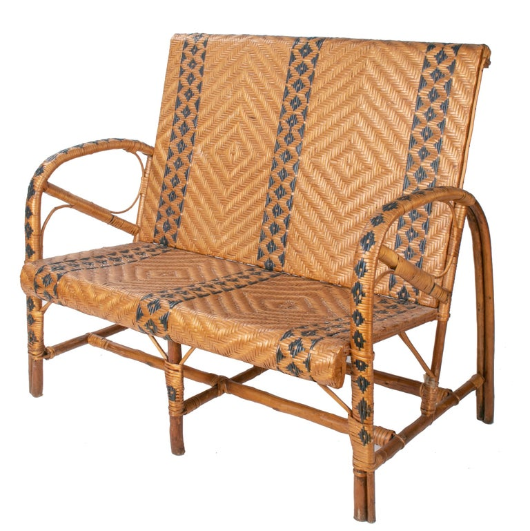 1970s Spanish bamboo and wicker two-tone set comprised of three armchairs, a sofa and a table. Geometric decoration that extends from top to the base of the legs.  Dimensions: Armchairs 90 cm height, 52 cm length, 58 cm width Table 67 cm height,