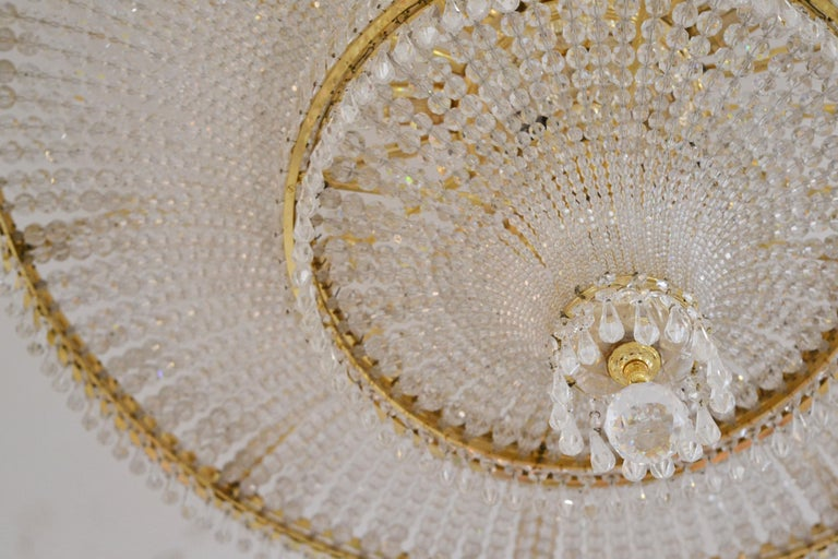 This spectacularly designed ceiling light is pure luxury and inspired by the palace and castle lights of the last centuries, in style of Empire and Regency.   It is crafted from hundreds of pieces of Swarovski crystal and a gilt brass frame.  It is