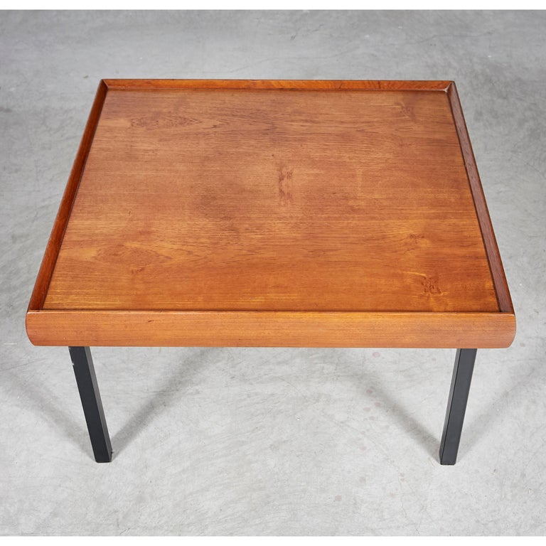 Vintage 1970s square teak wood coffee table with black metal legs. Newly refinished condition. Marked underneath.