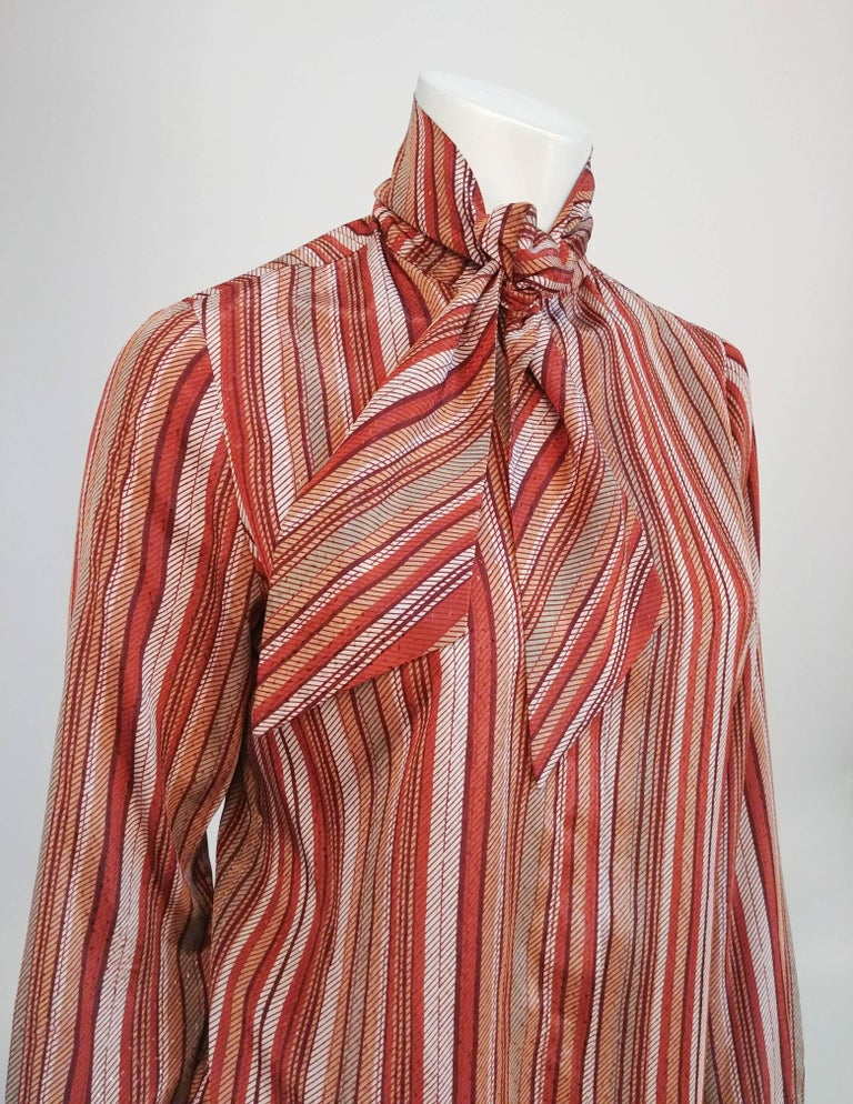 1970s St. John Neck Tie Striped Blouse. Striped orange blouse with tie front collar and hidden packet buttons.