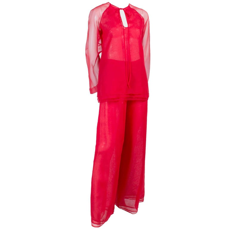 This red chiffon evening ensemble was designed by Stephen Burrows in the 1970's.  This evening dress alternative outfit includes a red chiffon tunic with a tiered hemline that ties at the neck, and a pair of high waisted flowing chiffon pants with