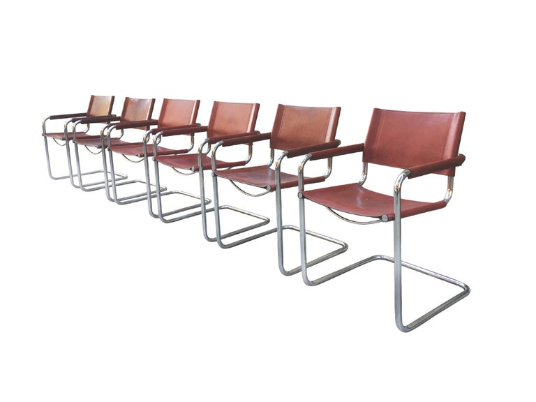 A handsome set of 6 dining chairs, made in the 1970s, with a nod to Bauhaus modernism, Matteo Grassi designs, and Campaign style furniture. The chairs consist of a chrome tubular frame and leather seating and back. The leather is stretched over the