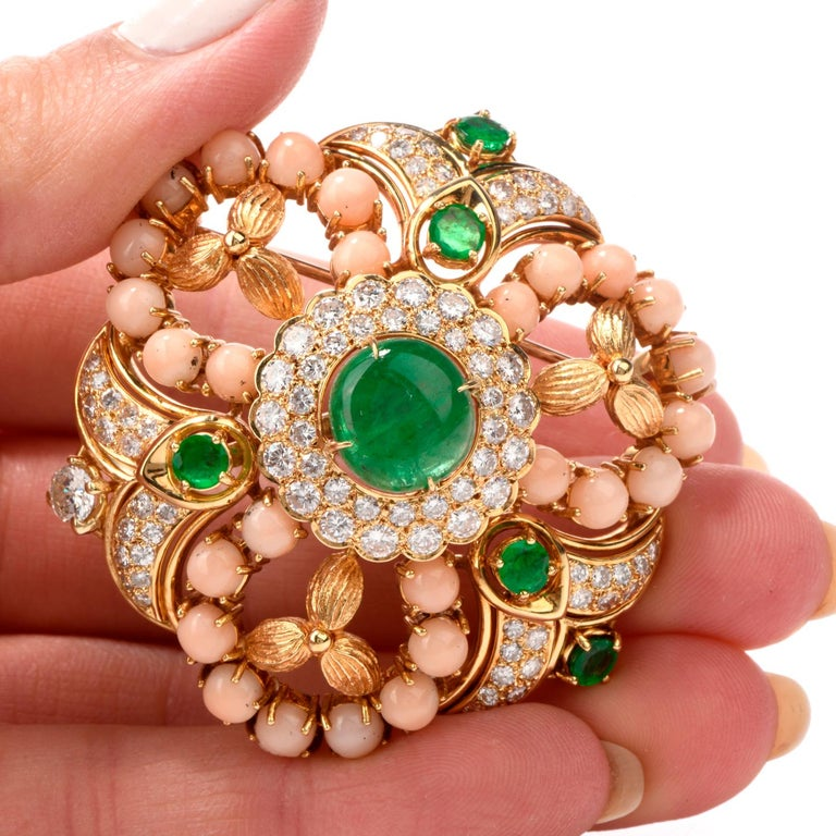 This Stylish coral Emerald and diamond Pin brooch is hand crafted in 18k yellow gold.   Centered with a genuine cabochon emerald weighing approx. 3.20 carats,  surrounded by exquisite diamonds and natural angel skin corals and 4 round cut emerald.