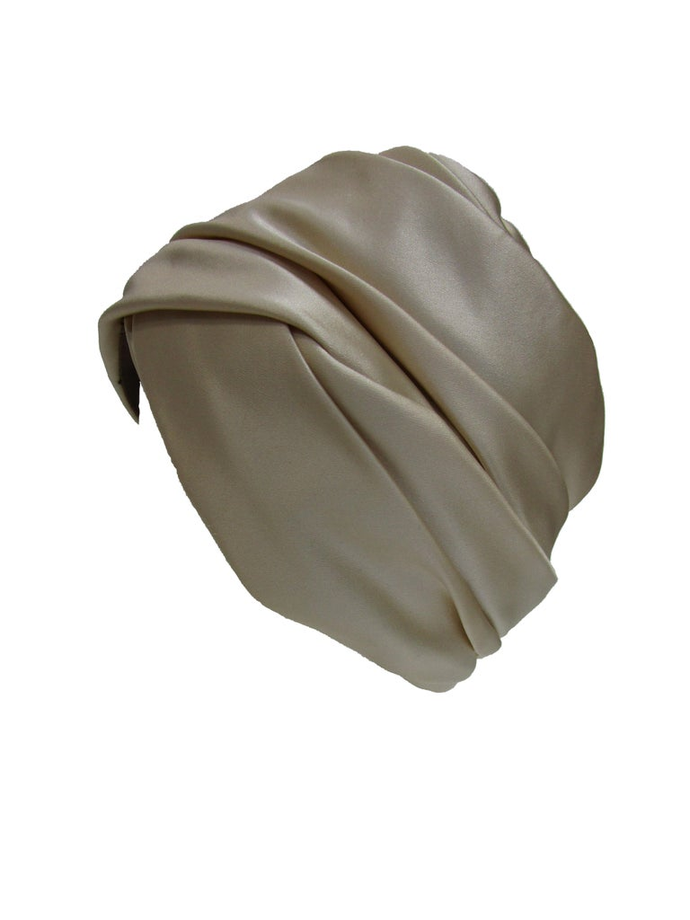 We adore this impeccably crafted silk turban by Irene of New York. It has a mesh lining and luxurious silk that wraps and pleats around the head. Turbans and scarves were a popular accessory in the 70s.