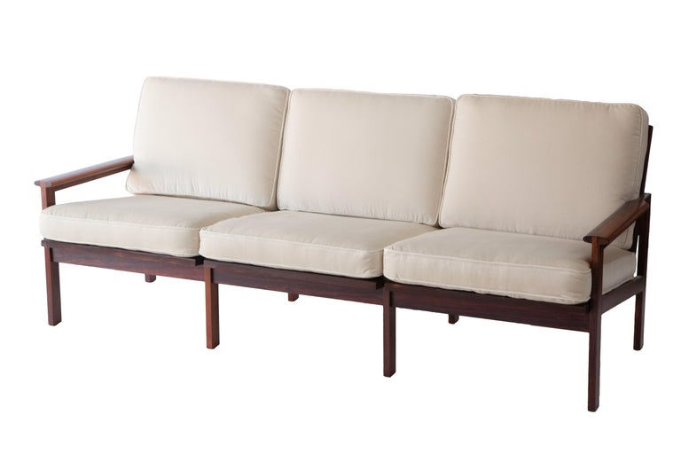A newly reupholstered sofa in the style of Finn Juhl. A glowing exotic rosewood frame. Sturdy with webbing and loose cushions.