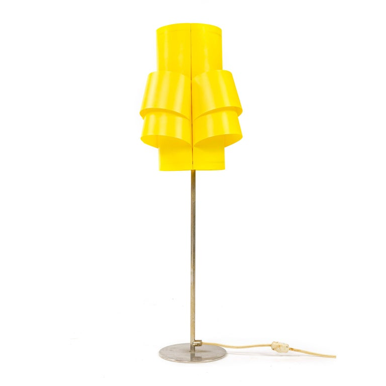 An electric lighting device having a shade of folded and formed yellow plastic attached to an inner wire frame threaded on to its electrical socket. It's chromed metal base having a slender stem threaded into a circular weighted base with a separate