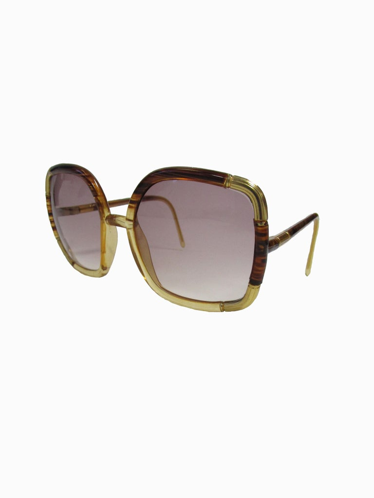 Classic Ted Lapidus sunglasses in a tortoise acrylic with gold accents and dusky lenses.  Lens Width-57mm Bridge Width- 15mm Temple (arm) Length - 149mm