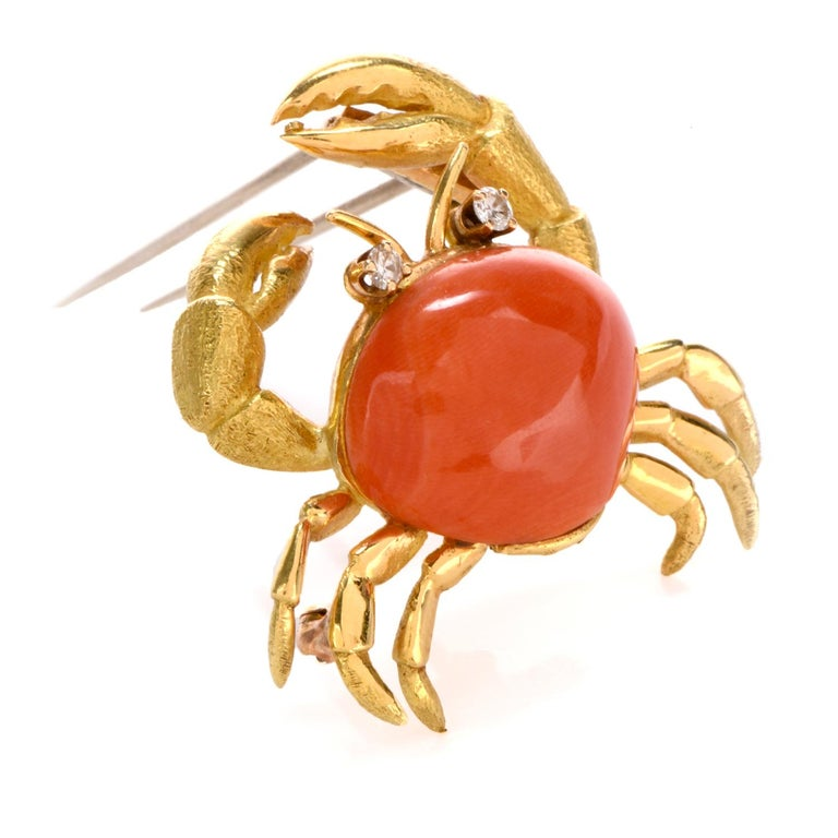 This excusite 1980's Tiffany and Co lapel pin displays a sand crab design motif and is crafted in bright glowing 18k gold. The brooch commands attention with a beautiful cabochon cut oval shaped genuine coral as the center focus and body and then