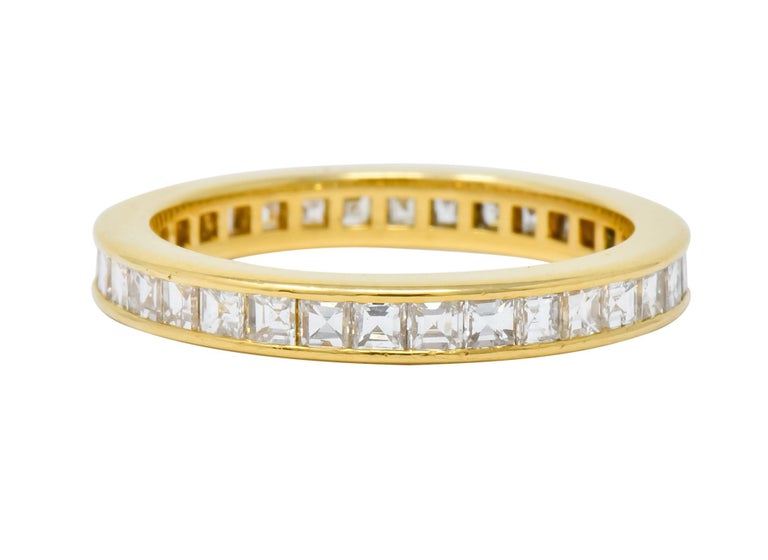 Eternity style band centering square step cut diamonds weighing 1.20 carats total, F/G color and VS clarity  Channel set fully around with high polished channel walls  Signed T & Co. for Tiffany & Co. and stamped 750 for 18 karat gold  Circa