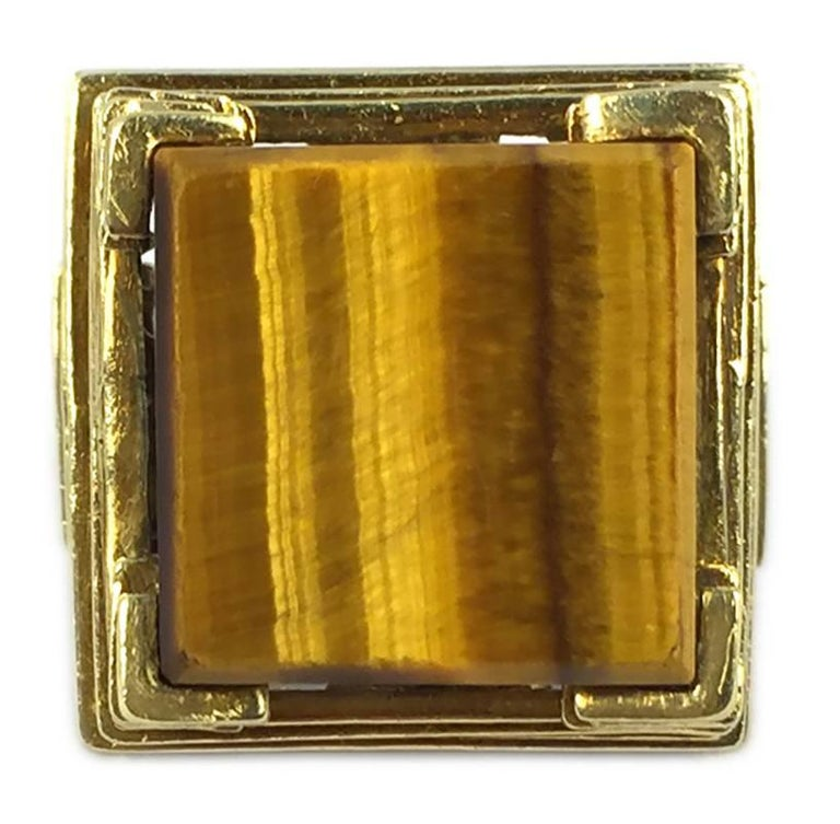 An unusual cocktail ring, showcasing a cubic tiger eye element, supported by a pyramidal step structure in 18kt yellow gold. Circa 1970.
