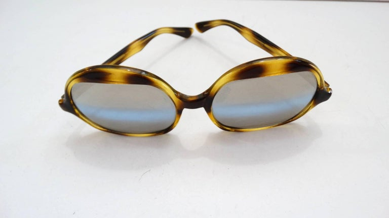 Channel your inner Elton John with our amazing 1970s tortoise oversized sunglasses! Made of a yellow and brown spotted tortoise enamel. Unique shaped lenses, rounded at the top and flat on the bottom. Grey colored lenses with bluish grey stripe