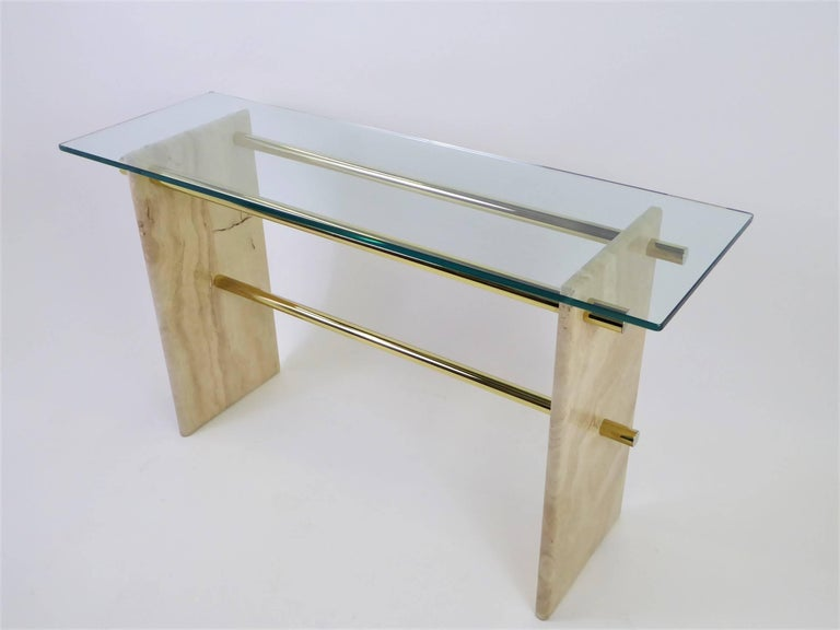 Unique and elegant, Minimalist and open Italian travertine console with fat brass rod stretcher supports, topped with a 1/2 inch thick glass. 1970s styling similar to later 1980s Artedi designs. Rods unscrew for traveling. Monolithic travertine