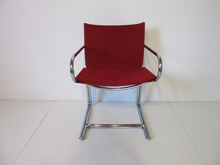 A set of four red upholstered sling style cantilevered arm chairs with bent tubular chrome frames, comfortable and compact from the 1970s. Can be used in the dining room, game room or business environment in the manner of Marcel Breuer.