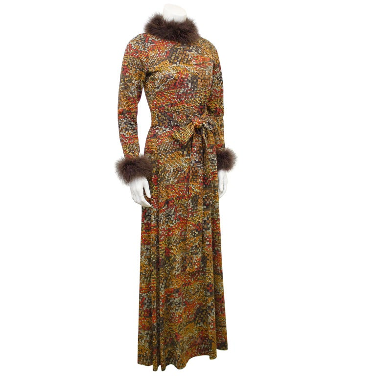 1970s jersey hostess gown from Italian designer Valditevere. Brown with an allover mid century modern print in shades of orange and beige. Long sleeves with brown marabou trim at neck and wrists. Optional waist belt. Invisible zipper up centre back.