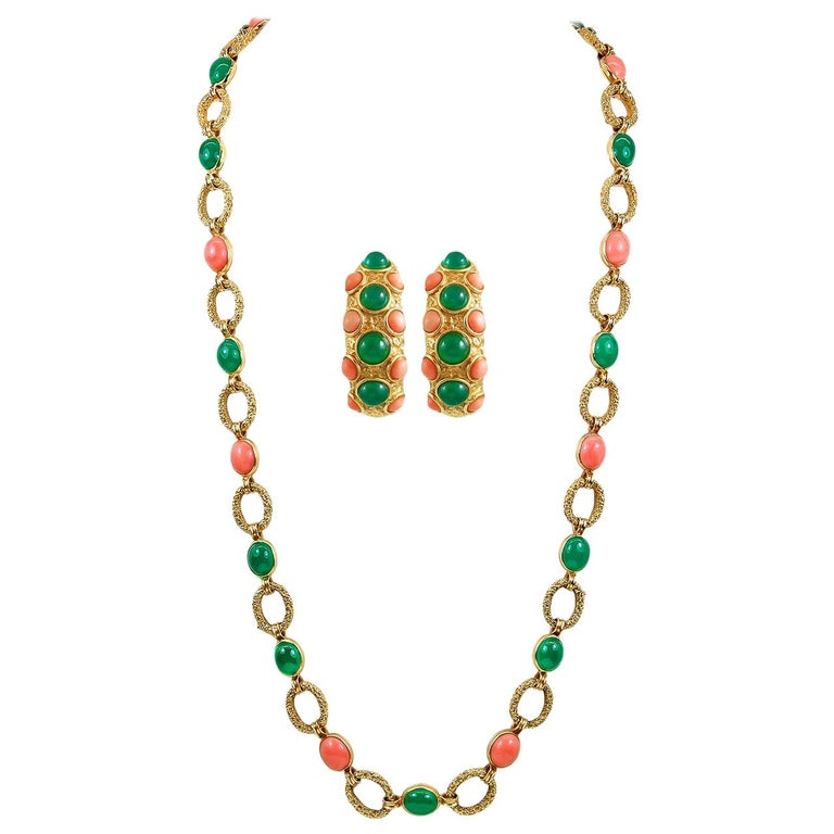 An exceptional suite by Van Cleef & Arpels that dates back to the 1970s, comprising a necklace, bracelet, and brooch, all exceptionally set with vibrant cabochon coral and chrysoprase orbs amongst 18k yellow gold textured designs. Signed Van Cleef &