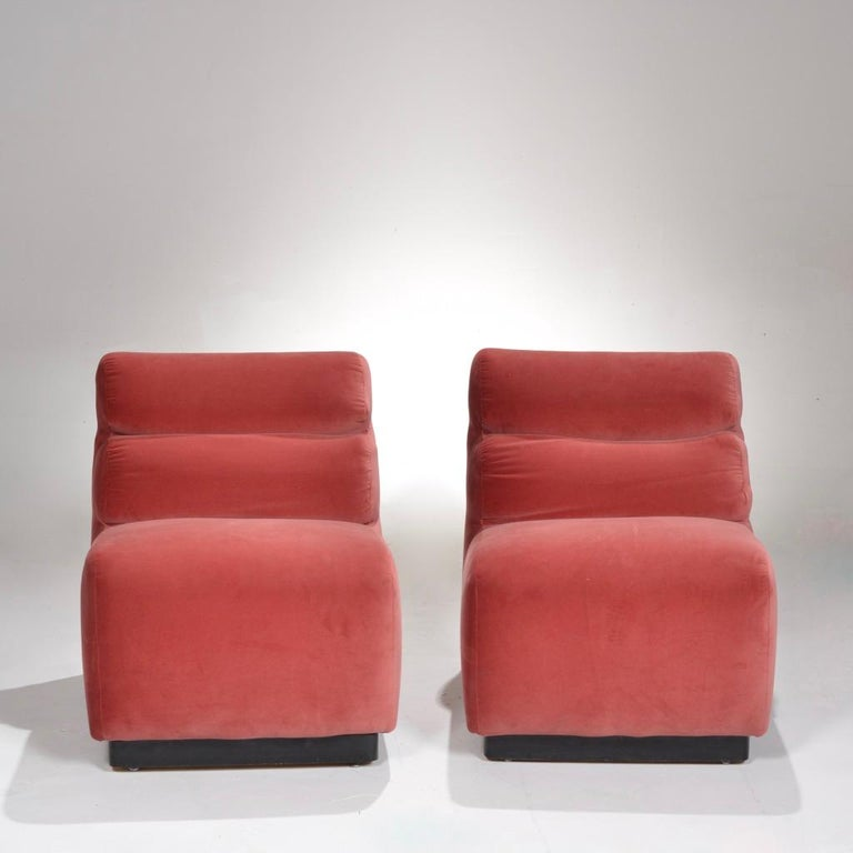 Pair of velvet slipper chairs by August Inc., 1978. Clean lines softened by subtle curves make these chairs equally sleek and plush. Great as lounge chairs or pushed together for a perfect loveseat. Newly upholstered.