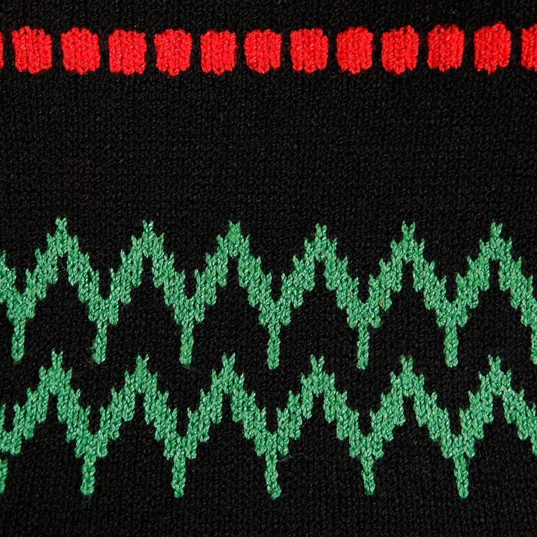 Darling vintage 1970s Adolfo knit sweater tank top in red, green and black. Colorful zig zag design. Unlined with rear partial zip closure. Fits like a modern size small. The bust measures 32-34