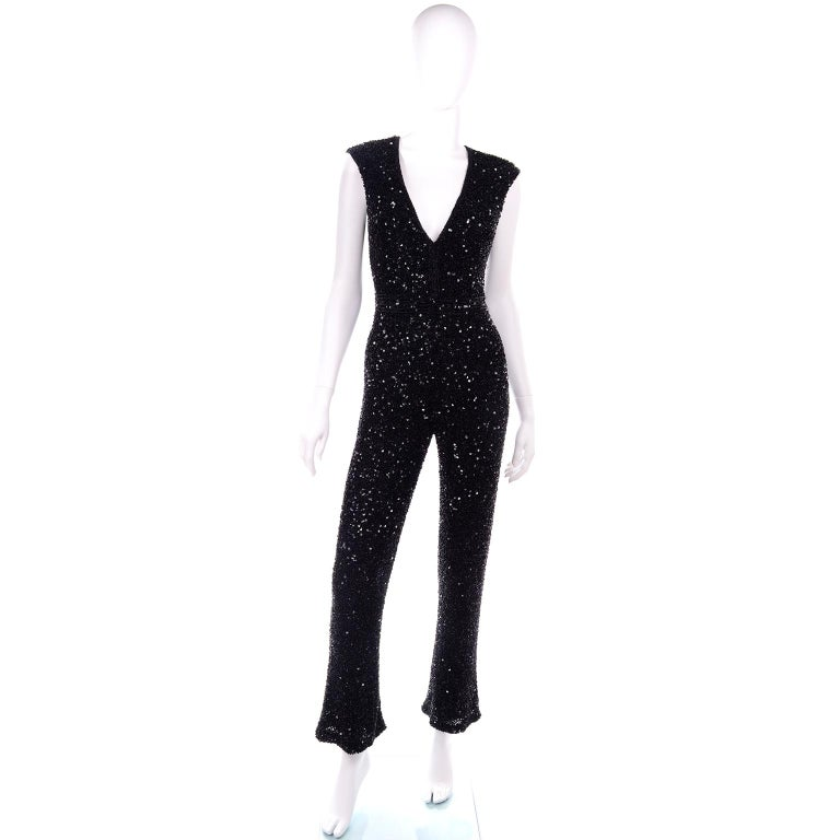 We love this 1970's sleeveless black evening jumpsuit with cute little kick flare hem. It is a great evening dress alternative for any holiday party! This deep v-neck jumpsuit is lined and covered completely with black beads and black flat sequins.
