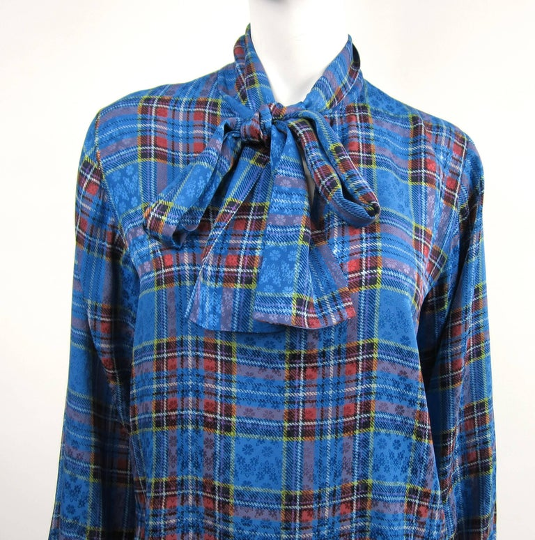 YSL Blue Silk Checkered Plaid Rive Gauche Silk Blouse with Scarf Bow on the neckline. No buttons, it slides overhead. Has Buttoned cuffs. Measuring- Up to 40 on the Bust - Up to 40 waist--- 25 inches long-- 23.5 long sleeve. This is out of a massive