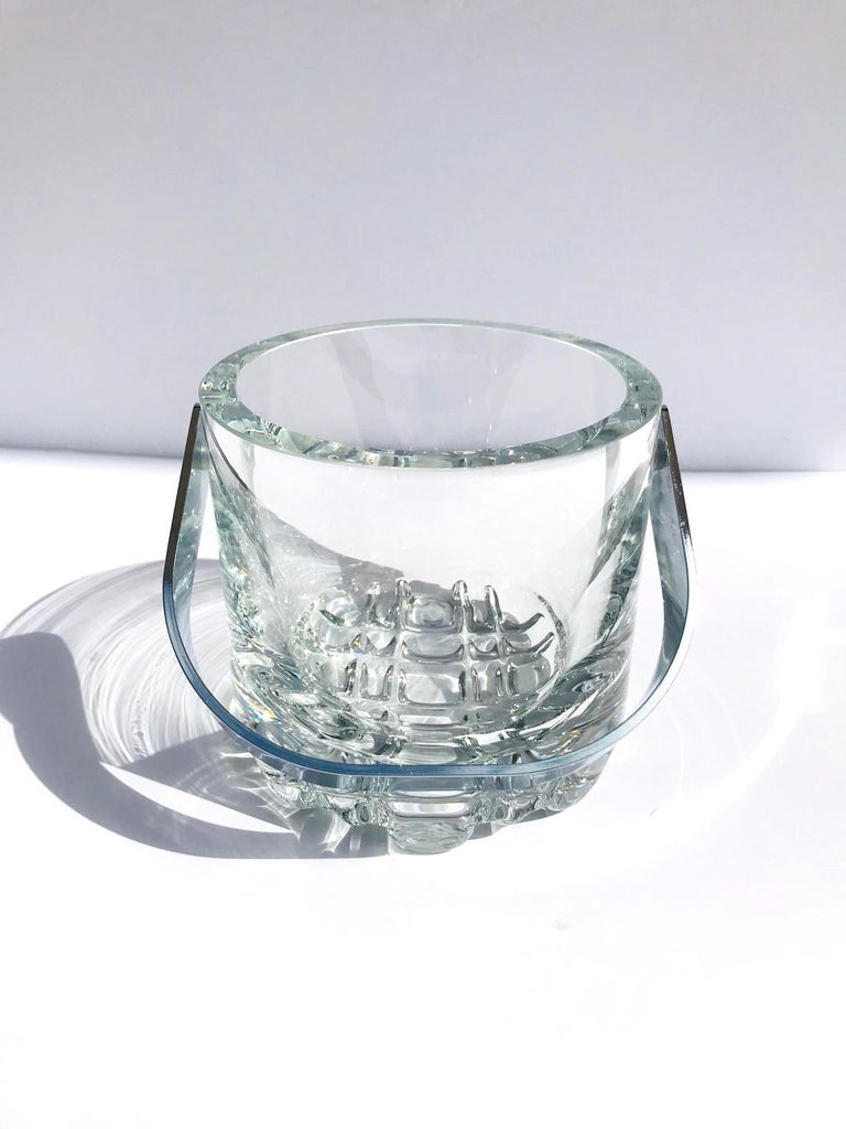 Exceptional Mid-Century Modern heavyweight crystal ice bucket. Heavy rounded edges with rock ice glass design along the base and with stainless steel handle. Makes a handsome addition to any barware set and can double as a wine cooler.