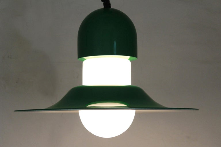 A rare 1970s vintage pendant. Bicolor structure (white and green) and extendible electrical wire (up to one metre). White opaline glass light globe and metal lampshade structure. In excellent conditions with only few signs of time. Electrical parts