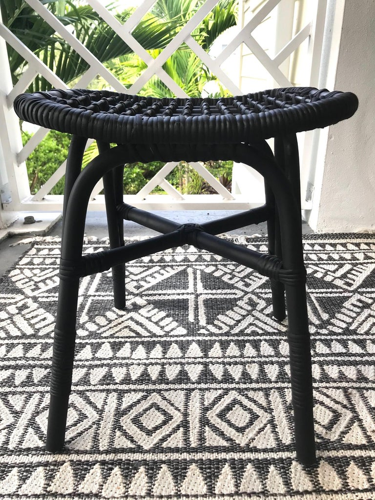 Vintage Indonesian handcrafted stool and ottoman made of sustainable bamboo and knotted rattan. Hand painted in black with a satin matte finish. The stool mixes the best of artisanal craftsmanship with Mid-Century Modern design. It features a curved