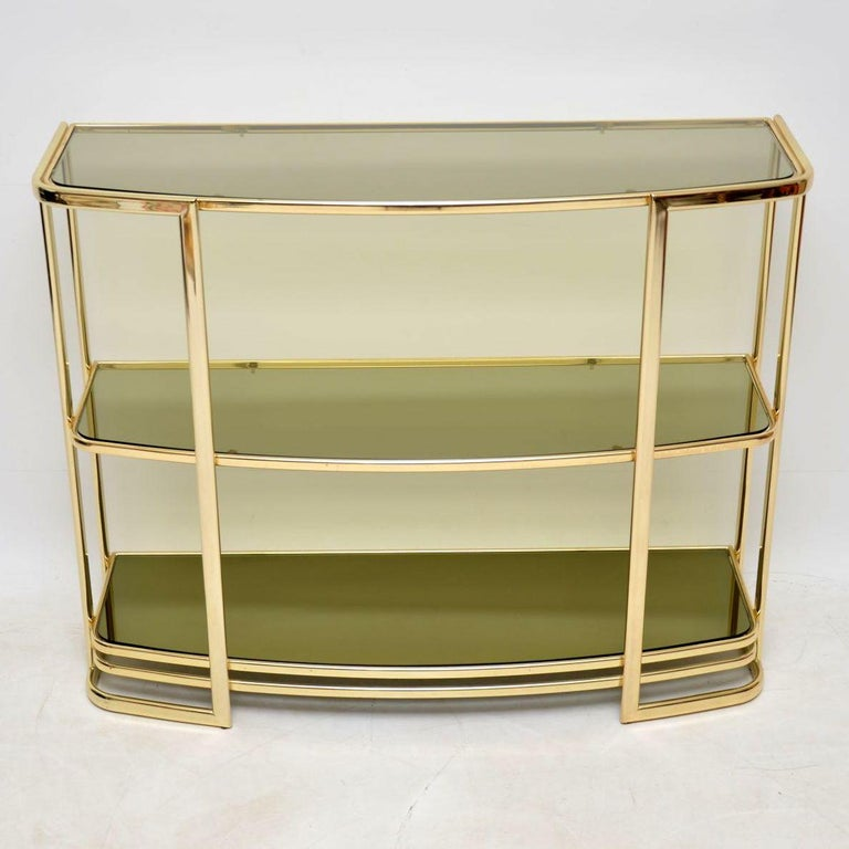 A beautiful and very well made vintage brass wall unit, this was made in Italy and it dates from around the 1970s. It's in great condition for its age, with only some extremely minor wear here and there. It has two smoked glass upper shelves, and