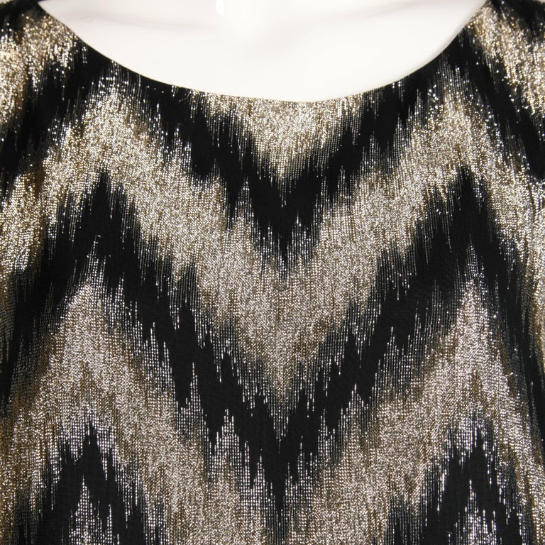 Awesome 1970s vintage caftan in a metallic gold + black zig zag design. Fully lined with no closure (pulls on over the head). 25% metallic, 75%, rayon. The lining is 100% polyester. Free size. The total length measures 55