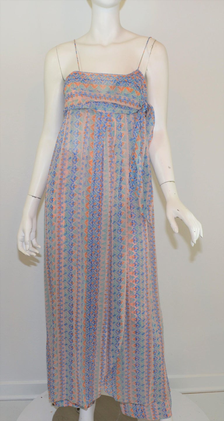 Stephen Burrows three-piece set includes: dress, shrug cover, and pants. The set features a multicolored print throughout atop a neutral background. Dress has a surplice neckline with hook-and-eye fastenings and tie at the left side of the bust.