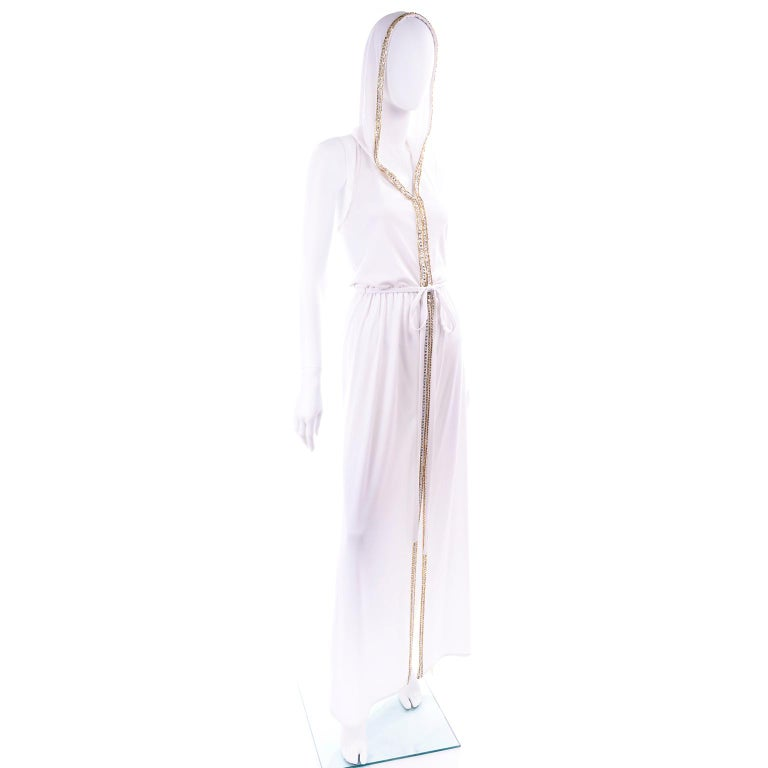 We fell in love with this vintage maxi dress when we found it!  This 1970's full length white jersey vintage dress is trimmed with rhinestones and gold beads and the best part - it has a hood!  The dress zips up the front and has a high slit up the